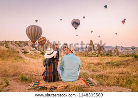 Happy young couple man and woman on vacation Turkey watching the Sunrise with millions of hot air balloons in Kapadokya, Cappadocia Turkey #1148305580