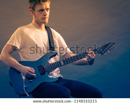 Young bearded man with electric guitar. Adult person is holding instrument and playing. Hobby, music concept, on grey #1148310215