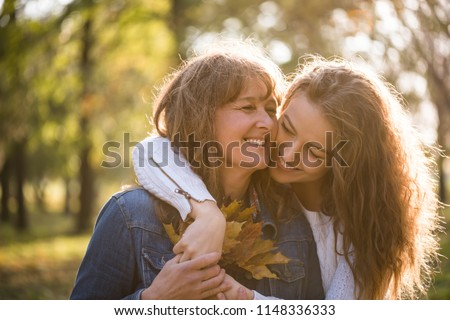 Portrait of cheerful senior woman holding autumn leaves with daughter Royalty-Free Stock Photo #1148336333