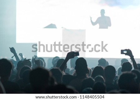 Crowd at music festival watching the concert, standing in front of bright stage lights #1148405504