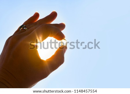 Vitamin D keeps you healthy while lack of sun. Hand holding yellow soft shell fish oil capsule against sun and blue sky on sunny day.  #1148457554