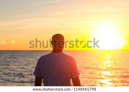a man stands with his back looking at the sea and the sunset #1148465798