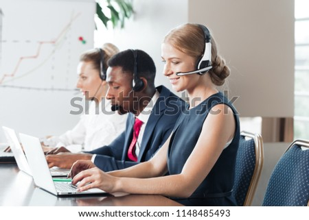 Attractive young woman working in a call center with his colleagues #1148485493