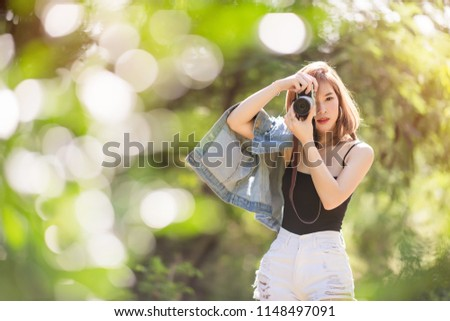 Portrait of asian woman is a professional photographer with mirrorless camera, outdoor portrait, free from copy space. #1148497091