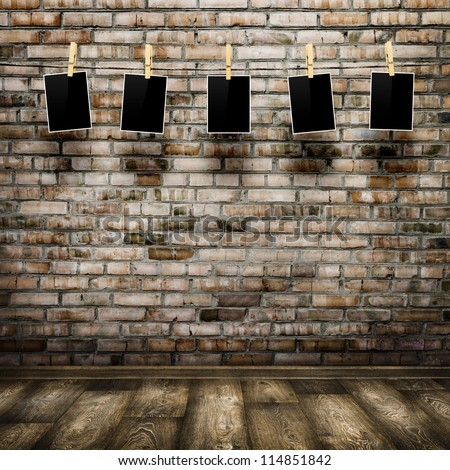 Photo frames with pins on rope over old aged brick wall and wood floor background