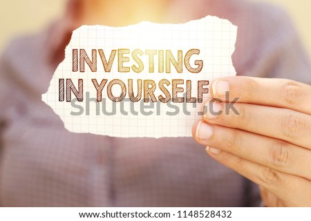 business woman holding tear paper with investing in yourself text Royalty-Free Stock Photo #1148528432