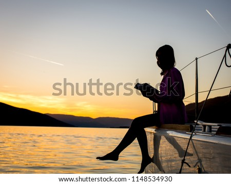 Young woman reading a book on a sailboat at sunset. Young woman reading a book in a luxury boat #1148534930