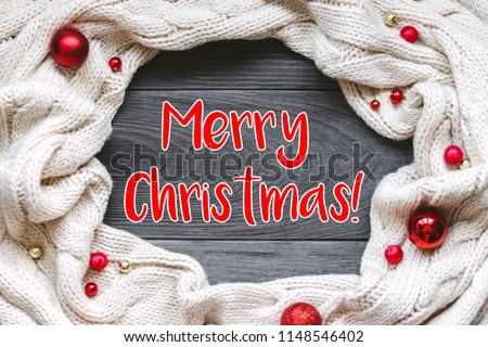 """Christmas card """"Merry Christmas"""" with frame decorated with knitted scarf on grey rough wooden background. Flat lay, top view, copy space. #1148546402"""