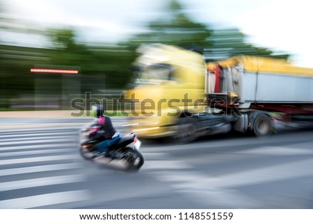 Dangerous city traffic situation with a motorcyclist and a truck  in motion blur #1148551559