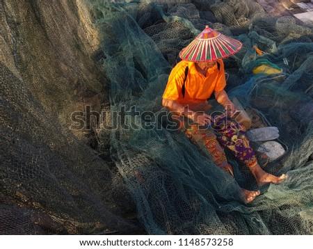 Sarawak 3 august 2018 a man sewing fishing net in Kampung Bako.  #1148573258