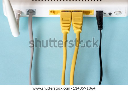 Connect an Ethernet Cable to a Wireless Router on light blue pastel. Ethernet, rj45 and electric cables, connected to router. Network concept #1148591864
