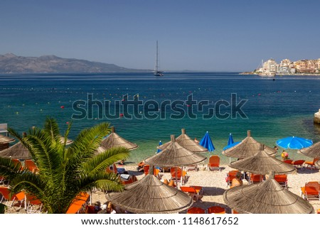 Beautiful beach with umbrellas for a holiday in Albania. Ionian Sea #1148617652