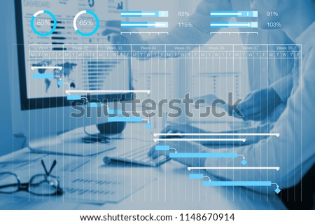 Project management scheduling concept with Gantt chart planning with tasks and milestones to monitor progress and deliverables with manager team in background working on computer in office Royalty-Free Stock Photo #1148670914