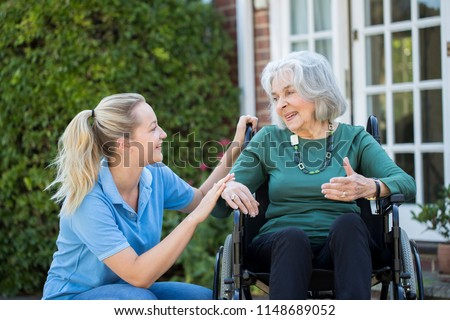 Carer Pushing Senior Woman In Wheelchair Outside Home #1148689052