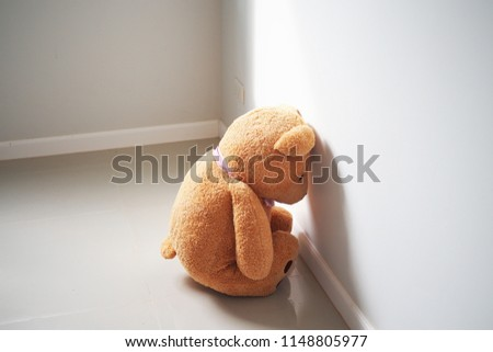Child concept of sorrow. Teddy bear sitting leaning against the wall of the house alone, look sad and disappointed.             #1148805977