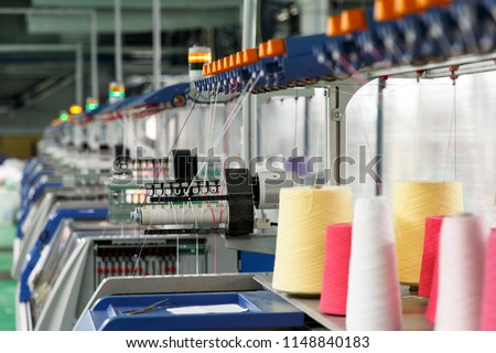 Textile industry with knitting machines in factory Royalty-Free Stock Photo #1148840183
