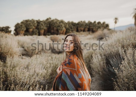 Smiling, beautiful hipster traveler girl in gypsy look and windy hair, in desert nature.  Artistic photo of young hipster traveler girl in gypsy look, in Coachella Valley in a desert valley in Souther #1149204089