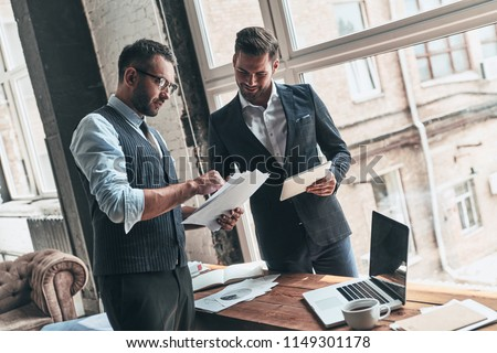 Team of innovators. Two young modern men in formalwear working together while standing indoors     #1149301178
