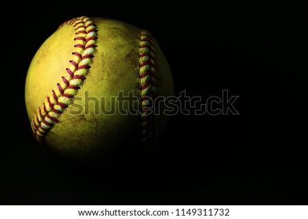 Yellow softball on a black background.