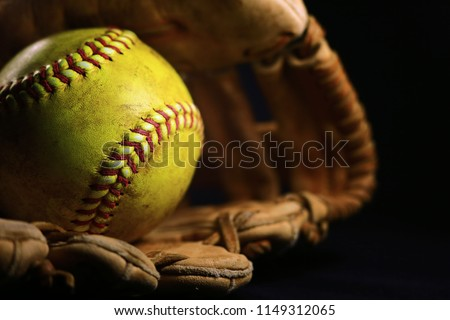 A yellow softball in an old, brown, glove.
