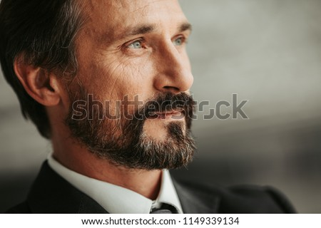 Close up pensive bearded businessman face looking away. Employer dreaming during job concept Royalty-Free Stock Photo #1149339134