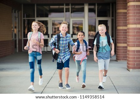 Group of school kids running as they leave elementary school at the end of day. Going home from school happy and excited. Back to school photo