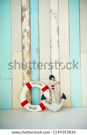 Composition on the marine theme with anchor and lifeline on wooden background