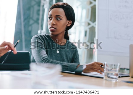 Portrait of young african businesswoman sitting at conference table looking at colleague during meeting. Female executive at boardroom meeting. #1149486491