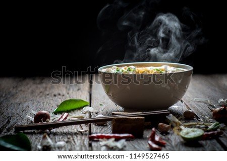 Noodles with steam and smoke in bowl on wooden background, selective focus. Asian meal on a table, junk food concept #1149527465