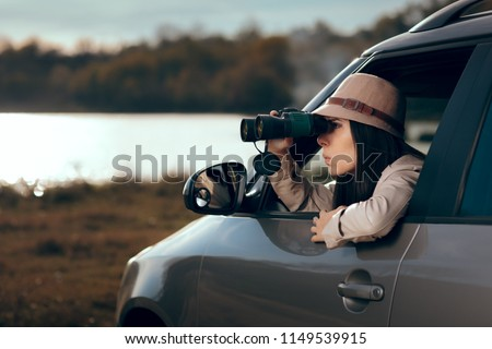 Female Detective Spying with Binocular from a Car. Secret agent private investigator looking for evidence in infidelity case  Royalty-Free Stock Photo #1149539915