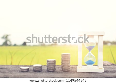 Stacked of money coin and hourglass on wood table, time to save money concept. #1149544343