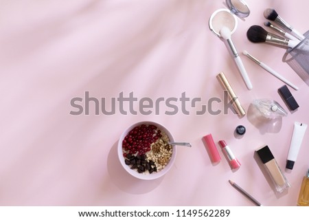 Top view of elegant woman make up table with pink and white accents and shadows on background, female morning with healthy breakfast oat flakes with berries, flat lay and copy space #1149562289