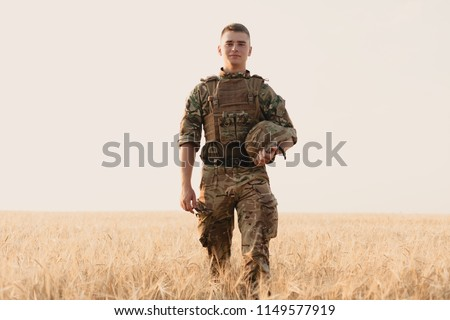 Soldier man standing against a field. Portrait of happy military soldier in boot camp. US Army soldier in the Mission. war and emotional concept. Royalty-Free Stock Photo #1149577919