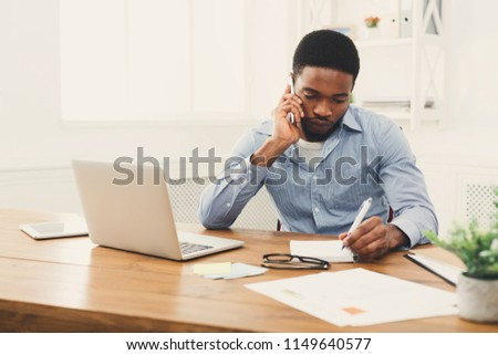 Young black businessman talking on mobile phone and making notes while working on laptop in modern white office, copy space #1149640577