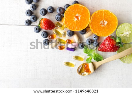 Multivitamins and supplements with fresh and healthy fruits on white wooden background. #1149648821