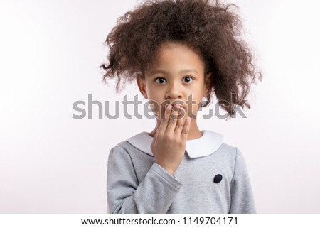 little black-haired girl has said a bad word. closeup portrait. isolated white background. #1149704171