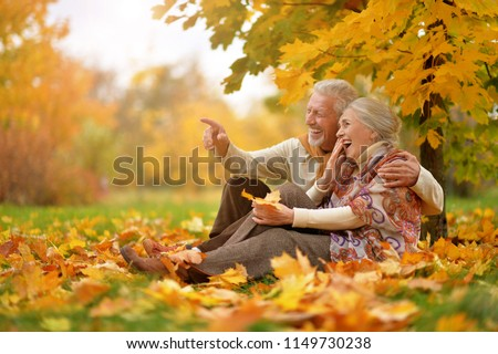happy Senior couple in autumn park sitting  #1149730238