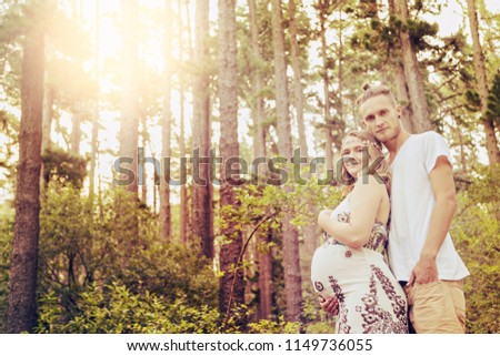 A young couple, - she very pregnant - walk through a sunny forest as she cradles her unborn child. #1149736055