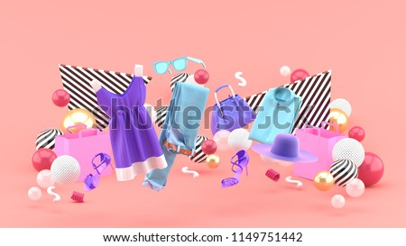 Dresses, pants, sweatshirts, hats, purses, high heels and sunglasses among colorful balls on a pink background.-3d rendering.