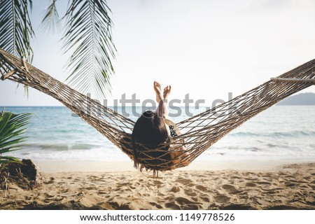 Summer vacations concept, Happy woman with white bikini, hat and shorts Jeans relaxing in hammock on tropical beach at sunset, Koh mak, Thailand #1149778526