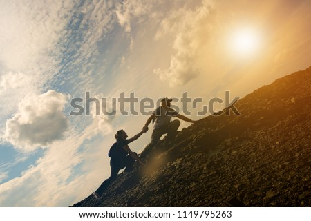 The joint work teamwork of two people man and girl travelers help each other on top of a mountain climbing team, a beautiful sunset landscape. The silhouettes on top of a mountain #1149795263