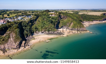 Aerial drone view of a beautiful coast town with sandy beaches and colorful buildings (Tenby, Wales, UK) #1149858413