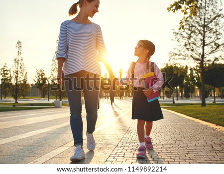first day at school. mother leads a little child school girl in first grade #1149892214