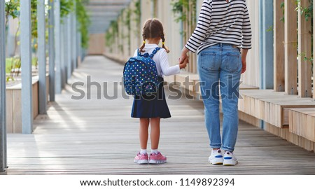 first day at school. mother leads a little child school girl in first grade #1149892394