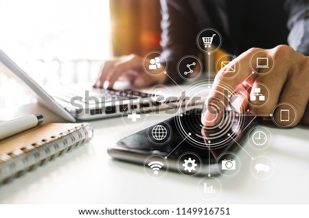 Digital marketing media in virtual screen.businesswoman hand working with mobile phone and modern compute with VR icon diagram at office in morning light   #1149916751