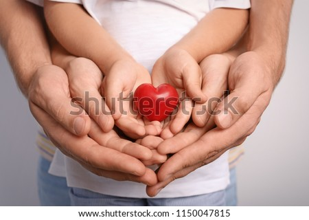 Family holding small red heart in hands together, closeup #1150047815