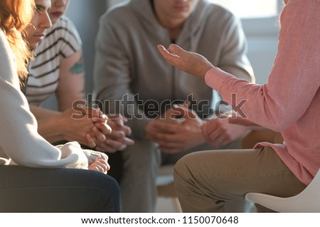 Close-up of a therapist gesticulating while talking to a group of listing teenagers during an educational self-acceptance and motivation meeting. #1150070648