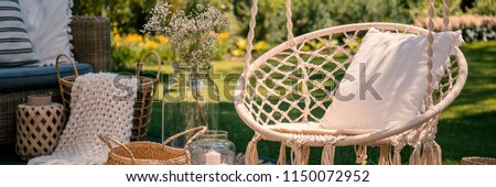 Pillow on hanging chair on terrace with blanket in basket next to flowers. Real photo