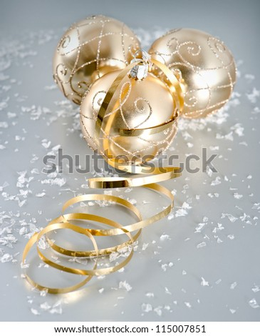 golden shiny christmas balls with snow decoration over silver background #115007851
