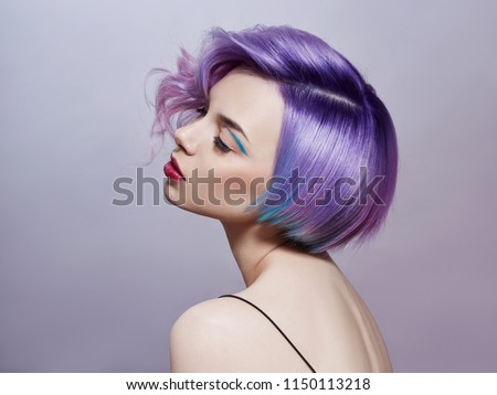 Portrait of a woman with bright colored flying hair, all shades of purple. Hair coloring, beautiful lips and makeup. Hair fluttering in the wind. Sexy girl with short  hair. Professional coloring #1150113218